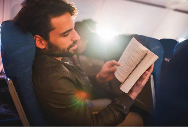 uomo in un aereo che legge un libro