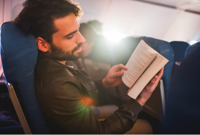 man reading a book in a plane
