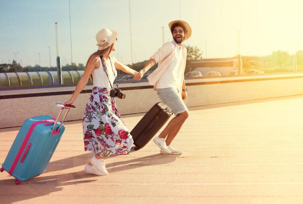 coppia che arriva a destinazione con le valigie